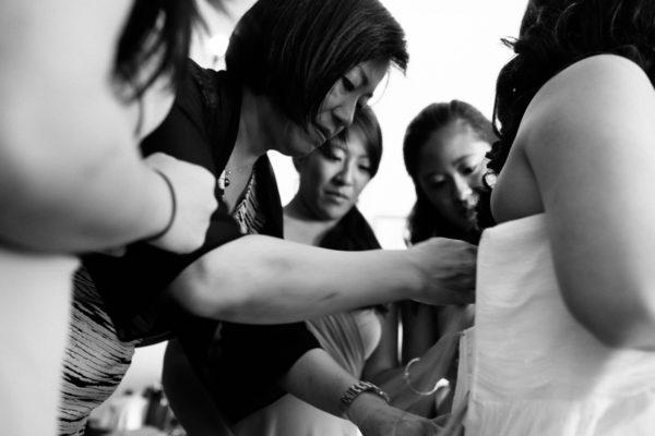 Bride putting on wedding dress black and white