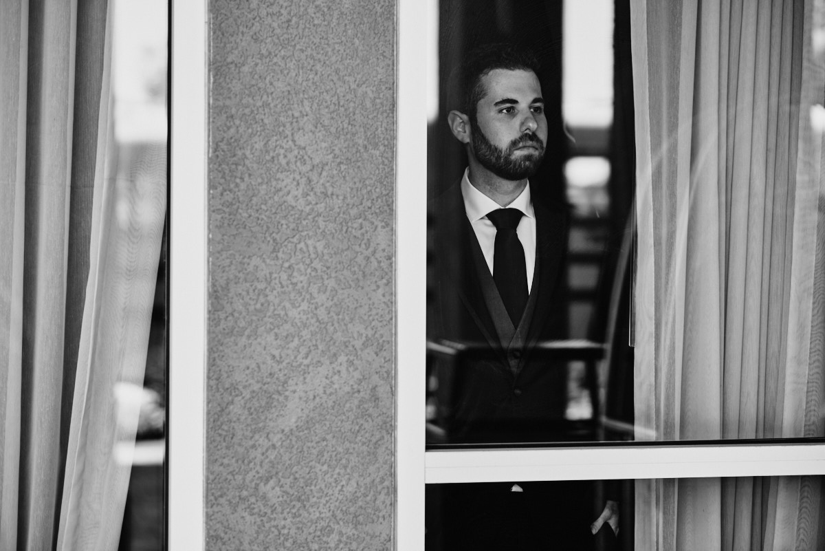 Groom looking out the window black and white